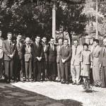 Primeiros trabalhadores da UFSC (1962). Acervo Agecom. Da esquerda para a direita: Hermes José Greipel (motorista), Adair Scharf (chefe de Compras), Josoé Fortkamp (diretor de Material), Ari Ramos Castro (tesoureiro), Antônio Nicoló Grillo (diretor de Pessoal), Antonio Miroski (diretor de Finanças), Zoélio Hugo Valente (escrituário), João José Caldeira Bastos (chefe de Legislação de Pessoal), Emanoel Campos (chefe de gabinete do reitor), Luiz Osvaldo d'Acâmpora (vice-reitor), João David Ferreira Lima (reitor), Aluizio Blasi (secretário geral), Hely Porto (escriturária), Teodoro Rogério Vahl (diretor da Imprensa Universitária), José Fernandes Neves Júnior (diretor de Serviços Gerais), Aldo Nascimento (motorista do reitor), Aldo Arnoldo Meira (auxiliar da Secretaria Geral), Manoel Roldão da Rosa (almoxarife) e Vivaldi Garofallis (diretor de Contabilidade). Identificação efetuada por Aluizio Blasi, em 11 maio 2010; Teodoro Rogério Vahl, em 17 jun. 2010; e Alcémelia Maria Cardoso, em jul. 2010, a pedido de Claudete Regina Ferreira.